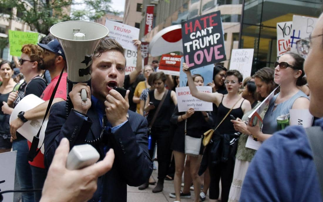 Protestors chant outside a downtown hotel in Boston, Wednesday, June 29, 2016, where Republican presidential candidate Donald Trump was holding a lunchtime fundraiser. Trump was scheduled to hold a rally later in the afternoon in Bangor, Maine. (AP Photo/Bill Sikes)