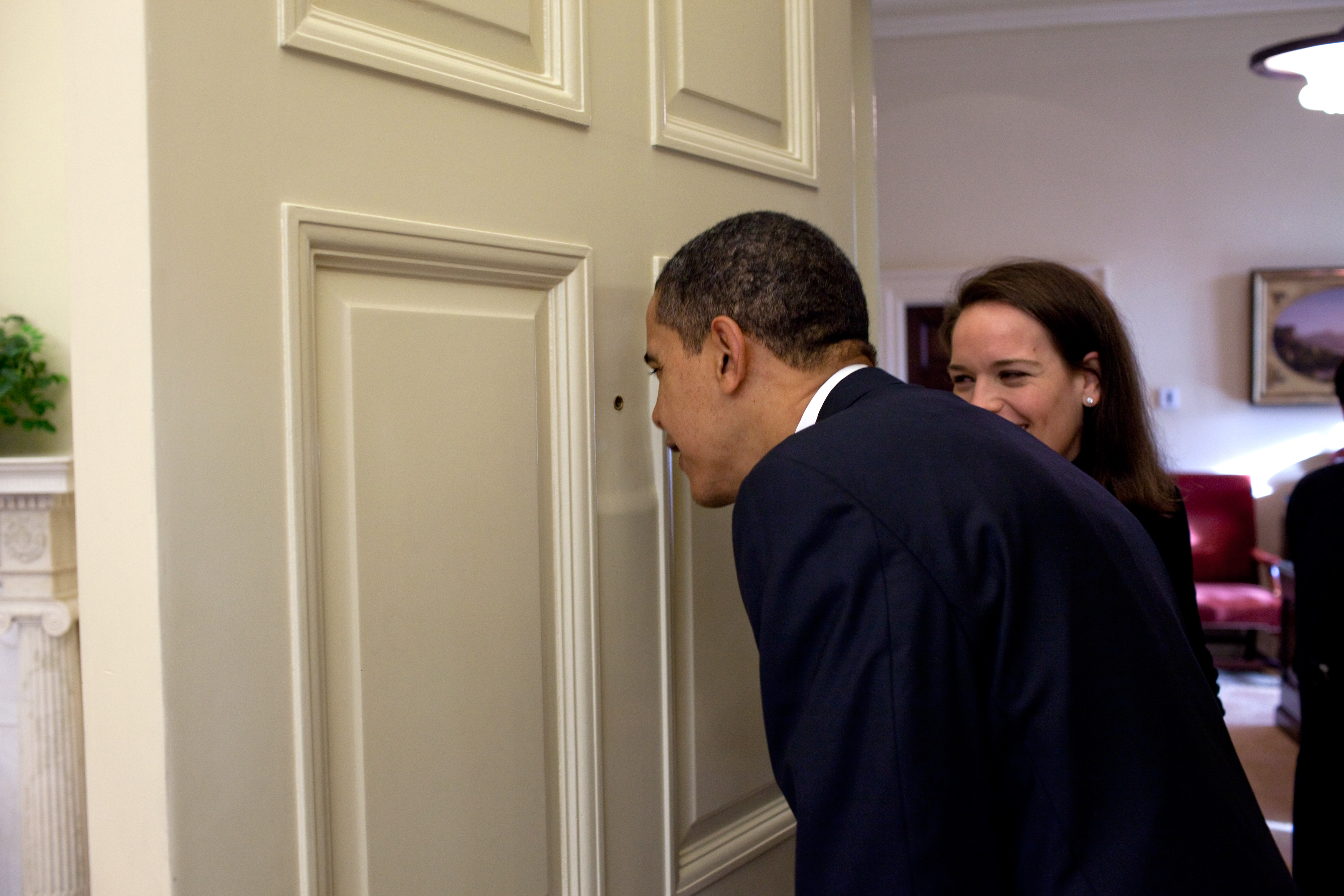 President Barack Obama looks through the Oval Office door peephole as his personal secretary Katie Johnson watches 3/12/09. Official White House Photo by Pete Souza